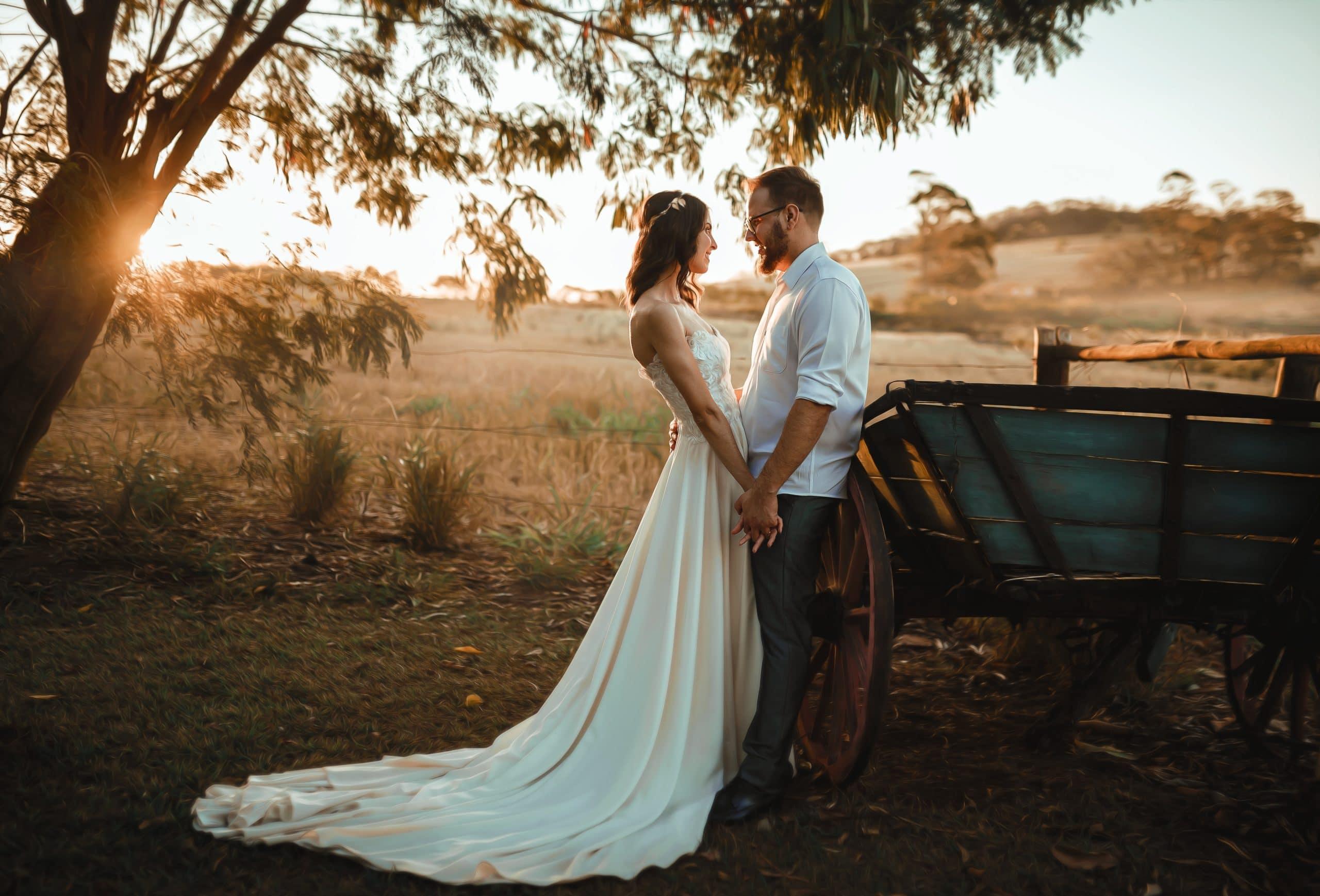 Un couple main dans la main adossé contre une charrette, le soleil se couchant derrière eux.