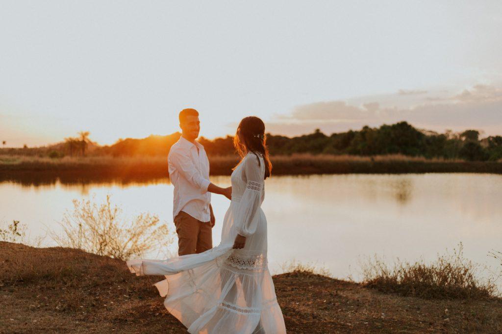Un couple d'amoureux au bord de l'eau se tenant la main avec le soleil couchant.