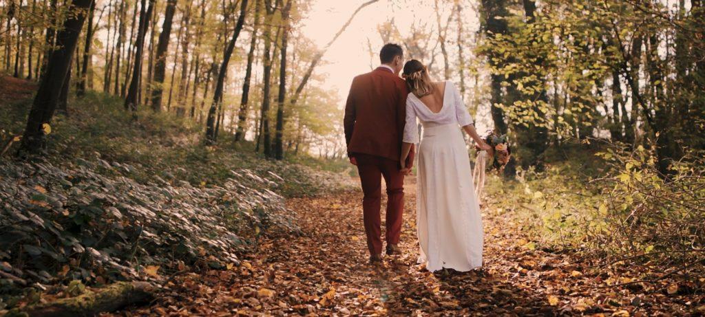 Les mariés marchant l'un contre l'autre dans la forêt.