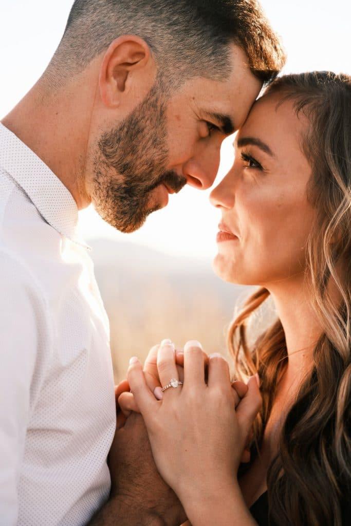 Un couple amoureux se regardant les yeux dans les yeux et se tenant les mains.